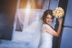 Bruid tegen een blauwe moderne de bouwachtergrond Stock Afbeeldingen