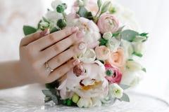 Bruid wat betreft huwelijksboeket die elegante huwelijksmanicure tonen royalty-vrije stock foto's