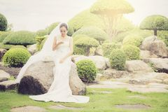 bruidaanraking op telefoon in huwelijkskleding op tuin Stock Foto's
