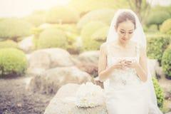bruidaanraking op telefoon in huwelijkskleding op tuin Royalty-vrije Stock Fotografie