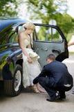 Bruidegom die bruid helpen om op haar schoenen te zetten Stock Foto