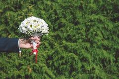 Bruidegom die bruids boeket houden Royalty-vrije Stock Foto's