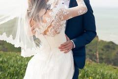 Bruidegom die de bruid in een huwelijkskleding een kussen oceanfront royalty-vrije stock foto's