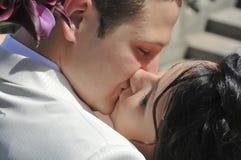 Bruidegom die de bruid kust Stock Foto's