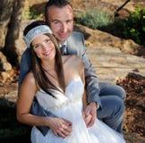 Bruidegom die de bruidzitting op een rots houden openlucht Royalty-vrije Stock Afbeelding
