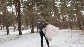 Bruidegom die of de gelukkige bruid spinnen draaien die haar houden in van hem dient de pijnboombos van het sneeuwweer tijdens sn stock video