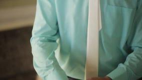 Bruidegom die de manchetten van zijn overhemdskleur Tiffany dichtknopen stock video