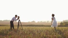 bruidegom die foto's van de springende bruid nemen bij de achtergrond van het de lentegebied stock video
