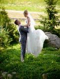 Bruidegom die hoge mooie bruid opheffen bij park Royalty-vrije Stock Afbeeldingen
