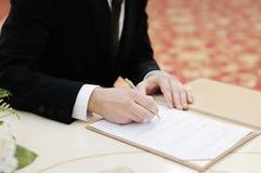 Bruidegom die huwelijksvergunning of huwelijkscontract ondertekenen Royalty-vrije Stock Foto's
