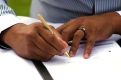 Bruidegom die huwelijksvergunning ondertekenen Stock Foto