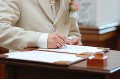 Bruidegom die huwelijksvergunning ondertekent Royalty-vrije Stock Foto's