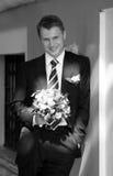 Bruidegom die met boeket wordt bevonden stock foto
