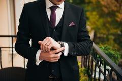 Bruidegom die modieuze horlogeband op zijn pols clasping Stock Fotografie