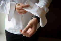 Bruidegom die op zijn cufflinks zet royalty-vrije stock foto