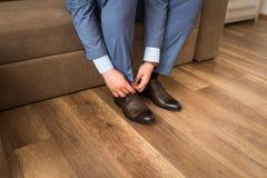 Bruidegom die schoenen bij huwelijk dag, het binden van het kant en het voorbereidingen treffen dragen Bedrijfsmens die zich omho Stock Foto's