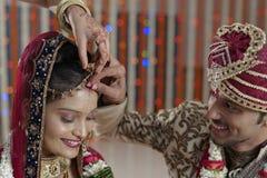 Bruidegom die Sindoor op het voorhoofd van de Bruid in Indisch Hindoes huwelijk zetten. royalty-vrije stock fotografie