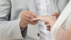 Bruidegom die trouwring op bride&#x27 zetten; s hand royalty-vrije stock fotografie
