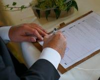 Bruidegom die voor huwelijk in burgerlijk registratiebureau ondertekenen stock foto