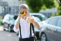 Bruidegom die zijn bruid met een onmiddellijke camera schieten stock foto's