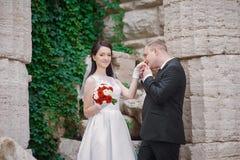 Bruidegom die zijn bruid op huwelijksdag kussen dichtbij boog stock foto