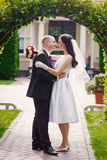 Bruidegom die zijn bruid op huwelijksdag kussen dichtbij boog stock fotografie