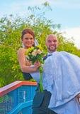 Bruidegom die zijn bruid vervoeren Stock Afbeeldingen