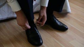 Bruidegom die zijn huwelijksschoenen zetten Handen die van huwelijksbruidegom klaar in kostuum worden stock videobeelden