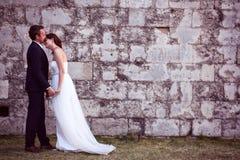 Bruidegom en bruid dichtbij bakstenen muur Royalty-vrije Stock Foto's