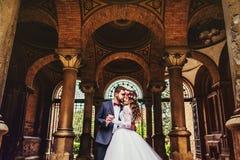 Bruidegom en bruid dichtbij de kolommen royalty-vrije stock foto