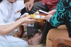Bruidegom en bruid die Chinese thee in traditionele Thaise huwelijksceremonie houden Concept huwelijk Stock Foto's