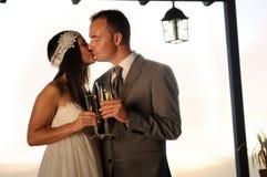 Bruidegom en bruid die en op een terras kussen roosteren Royalty-vrije Stock Afbeeldingen