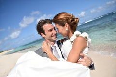 Bruidegom en bruid die op het strand omhelzen royalty-vrije stock fotografie