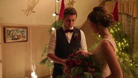 Bruidegom en bruid die trouwringen op overeenkomsten weddin ceremonie ruilen met bolslingers en het decor van de winterkerstmis stock videobeelden