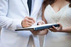 Bruidegom en bruid die in wit kostuum hun huwelijksvergunning ondertekenen Royalty-vrije Stock Foto's