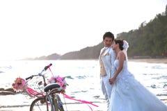 Bruidegom en bruid die zich op overzees strand naast oude klassieke fiets bevinden royalty-vrije stock fotografie