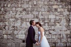 bruidegom en bruid het kussen dichtbij bakstenen muur Stock Afbeeldingen