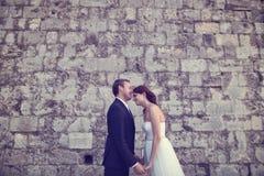 bruidegom en bruid het kussen dichtbij bakstenen muur Royalty-vrije Stock Afbeeldingen