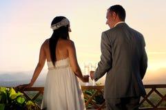Bruidegom en bruid het roosteren op een het contact achtermening van het terrasoog Royalty-vrije Stock Foto's