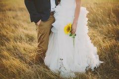 Bruidegom en bruid met zonnebloemen op het gebied Stock Foto