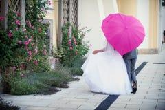 Bruidegom en bruid onder paraplu royalty-vrije stock fotografie