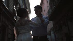 Bruidegom en bruid op een smalle straat stock footage