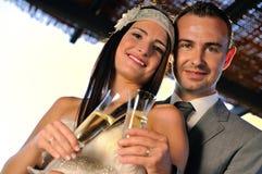 Bruidegom en bruid roosteren die op terras het vooruitzien glimlachen Royalty-vrije Stock Foto's