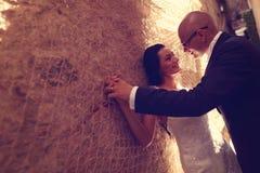 Bruidegom en bruid tegen een muur met schakelnet stock foto's