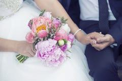 Bruidegom en bruidholdingshanden, met huwelijksboeket stock afbeeldingen