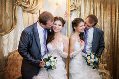 Bruidegom en de bruidtribune dichtbij een spiegel met een gouden kader Royalty-vrije Stock Foto's