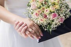 Bruidegom in kostuum en bruid in de holdingshanden van de huwelijkskleding Stock Foto's