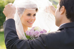 Bruidegom Looking At Bride met Liefde Royalty-vrije Stock Afbeeldingen