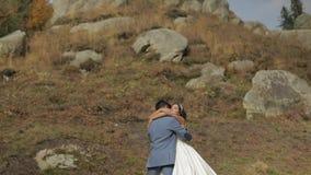 Bruidegom met bruid dichtbij bergheuvels Het Paar van het huwelijk Gelukkige familie in liefde stock videobeelden