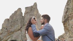 Bruidegom met bruid dichtbij bergheuvels Het paar van het huwelijk in liefde sunbeams stock videobeelden